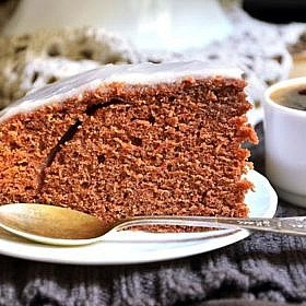 Chocolate and beer cake with yogurt glaze on black background.