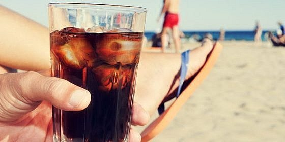 closeup of a young caucasian man hanging out on the beach with a glass with cola drink