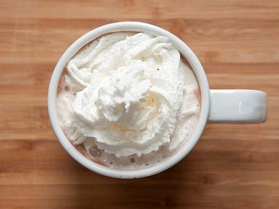 A cup of cocoa with whipped cream, sitting on a wooden surface.