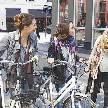 Group of women walking in Copenhagen. They are in their twenties and they are wearing smart casual clothes. Two of them are holding a bicycle, typical mode of transport in Denmark.